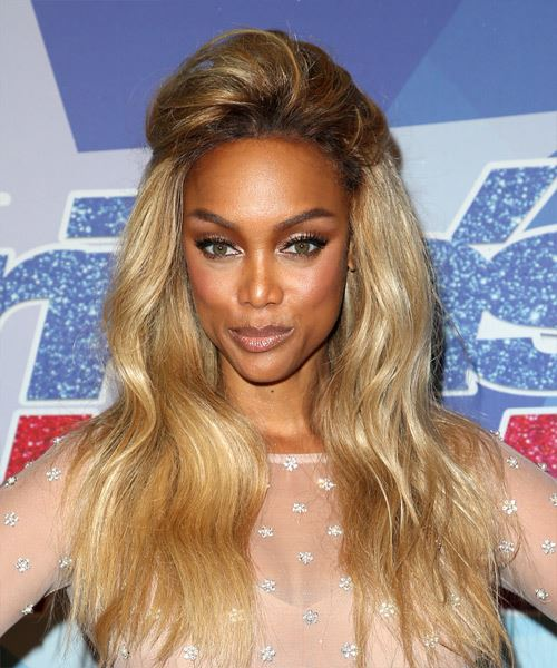 Tyra Banks wears a half up puff hairstyle in her long blonde hair