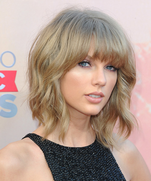 Taylor Swift Medium Wavy Casual Hairstyle with Blunt Cut Bangs - Medium Blonde (Caramel) Hair Color - side on view