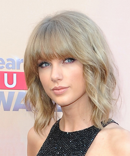 Taylor Swift Medium Wavy Casual    Hairstyle with Blunt Cut Bangs  -  Caramel Blonde Hair Color - Side on View