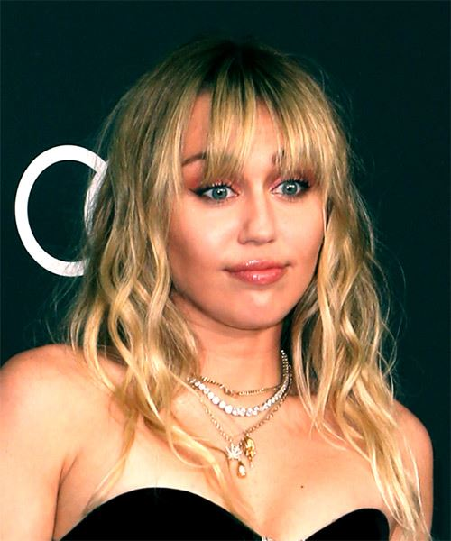 Miley Cyrus Medium Wavy Casual    Hairstyle with Blunt Cut Bangs  -  Blonde Hair Color - Side on View