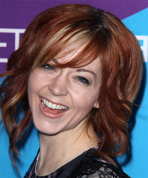 Lindsey Stirling Medium Wavy    Red   Hairstyle with Side Swept Bangs  and Light Blonde Highlights - Side on View