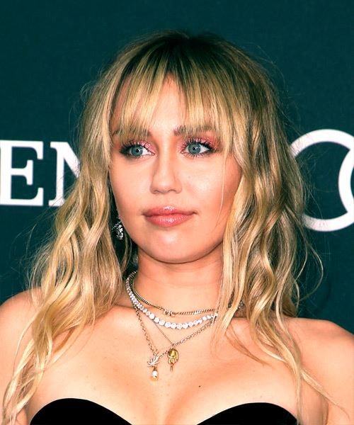 Miley Cyrus Medium Wavy Casual    Hairstyle with Blunt Cut Bangs  -  Blonde Hair Color - Side View