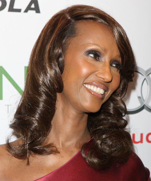 Iman Medium Wavy Dark Brown Hairstyle with Golden Brown Highlights and Side Swept Bangs